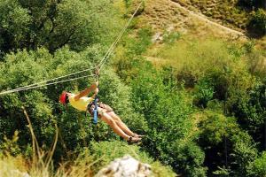 Zip line injuries: color photo of man soaring over treetops on zip line