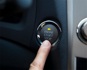 color photo of a finger pointing to a car's keyless ignition switch