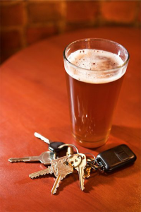 drunk driving: color photo of glass of beer and car keys on brown table
