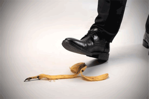 slip-and-fall: photo of man's foot in black shoe and black dress pants hovering over banana peel