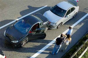 driverless cars: photo of two men and a woman looking at two cars involved in crash