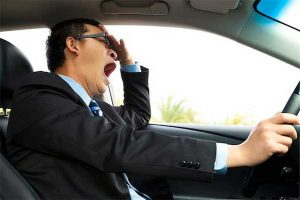 Photo of driver yawning behind the wheel of car