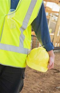 Workplace safety - photo of worker at building site wearing yellow reflective vest and holding yellow hardhat