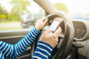 Distracted driving photo of arms of driver with one hand on steering wheel and the other operating a cell phone