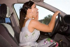 Photo of woman behind the wheel of a car yawning depicts growing problem fatigued driving poses on nation's roads